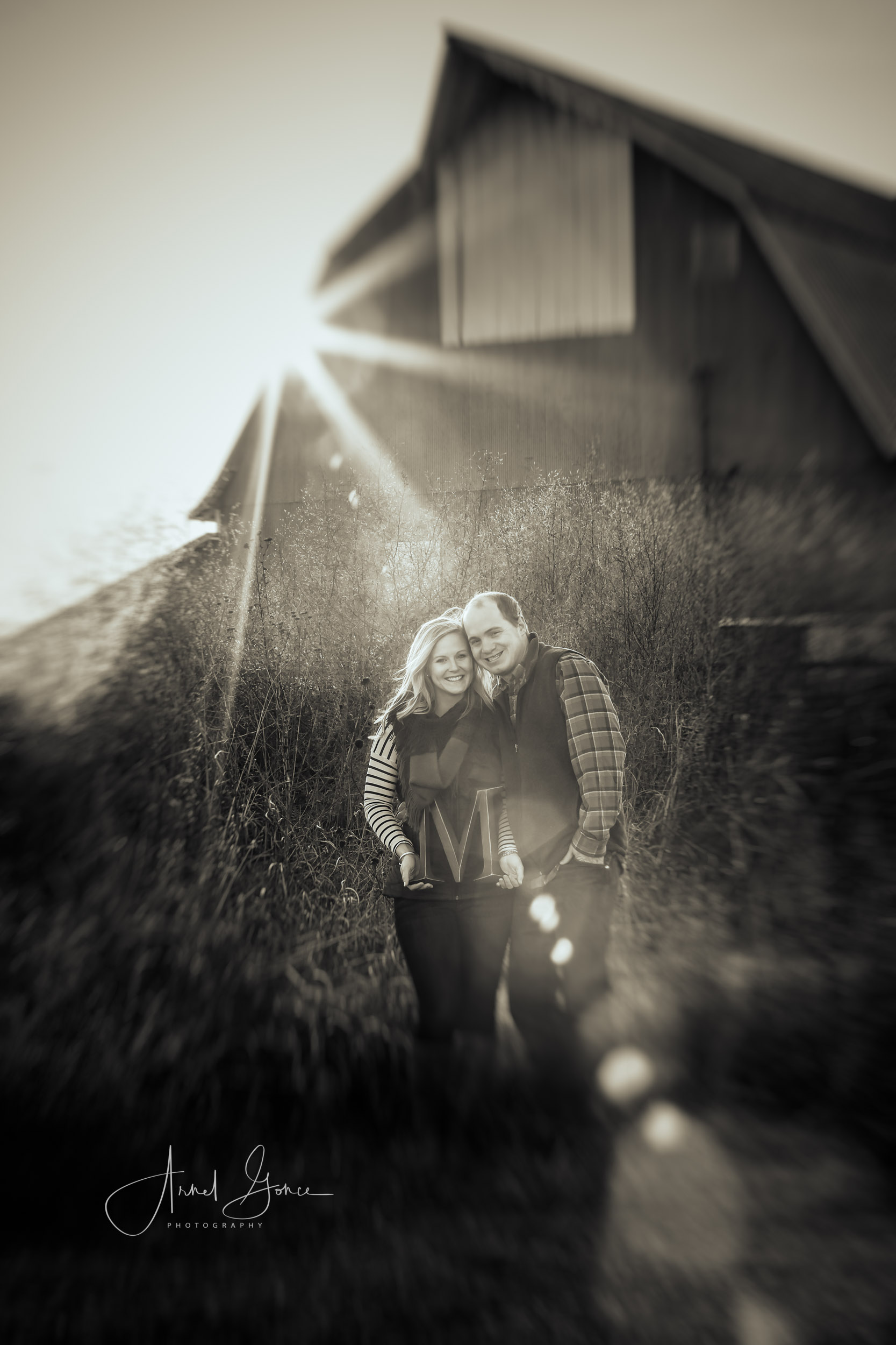 Starburst off of the barn during a photography engagement session in Edmond Oklahoma. The couple is holding the letter M to designate the last name.