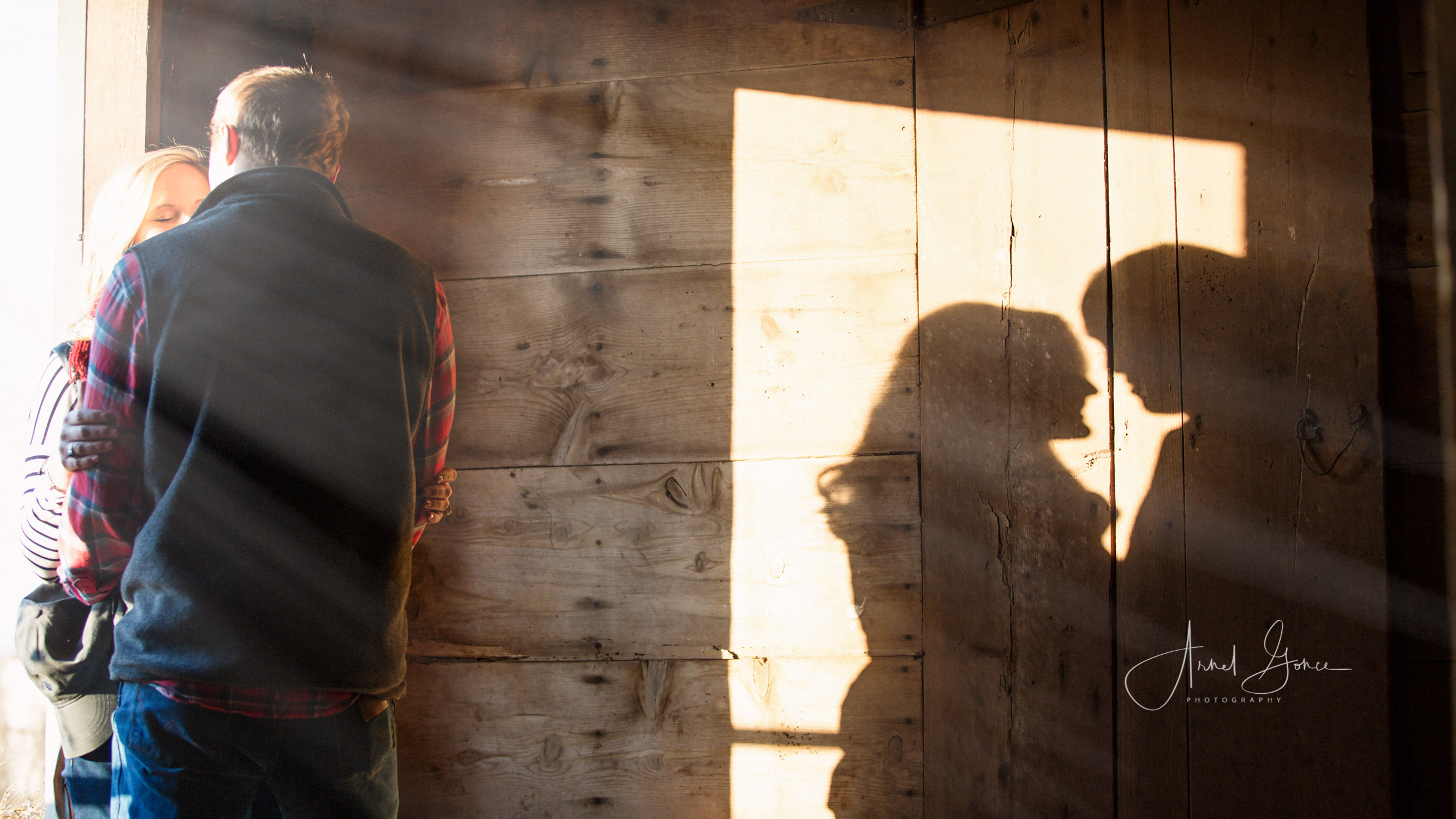 Couple in barn doorway with sunlight streaming over them casting a shadow on the wall behind them.