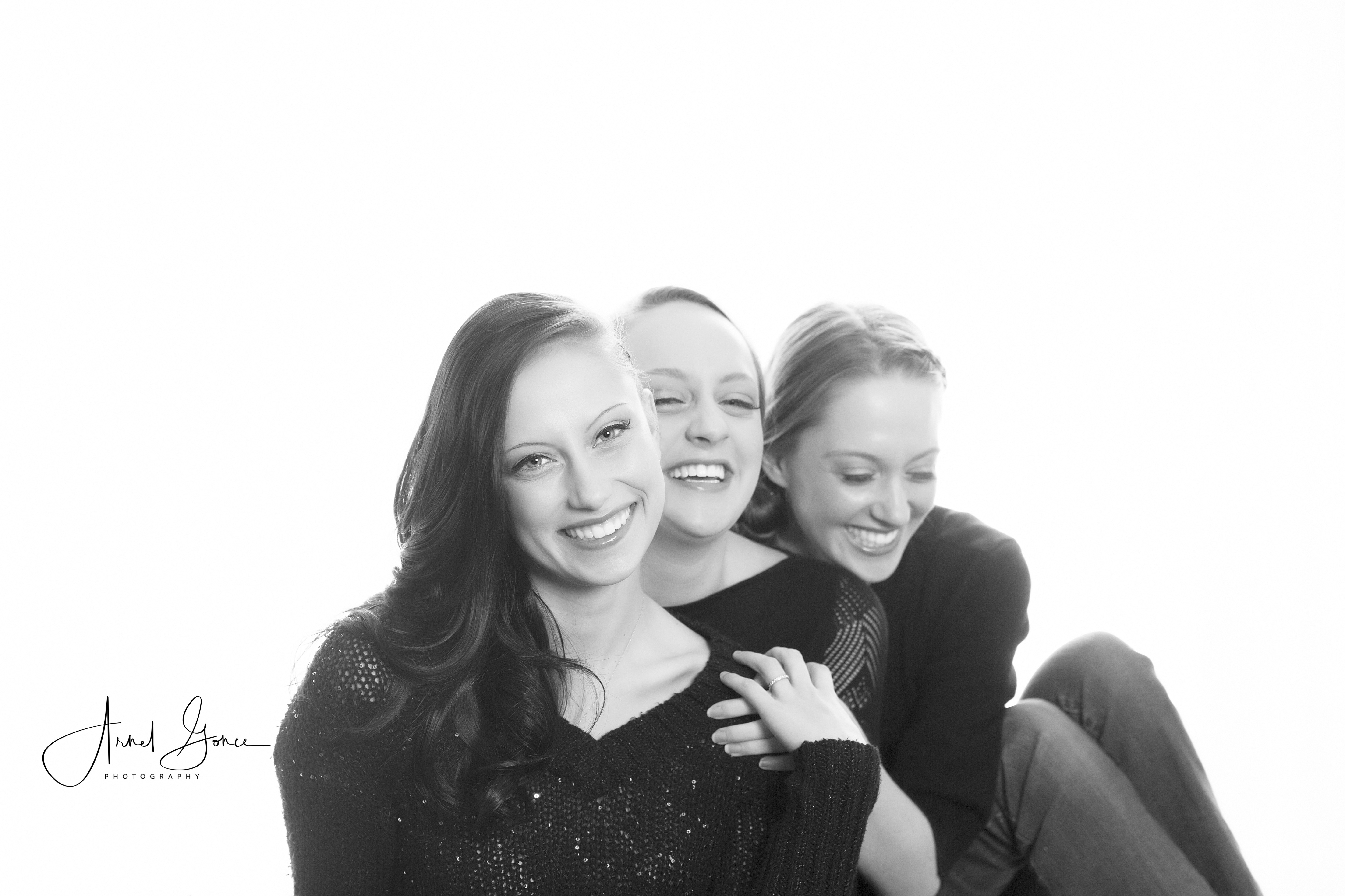 Three sisters in a backlit photograph sitting one in front of another laughing. Black and white image taken in studio and back lit.