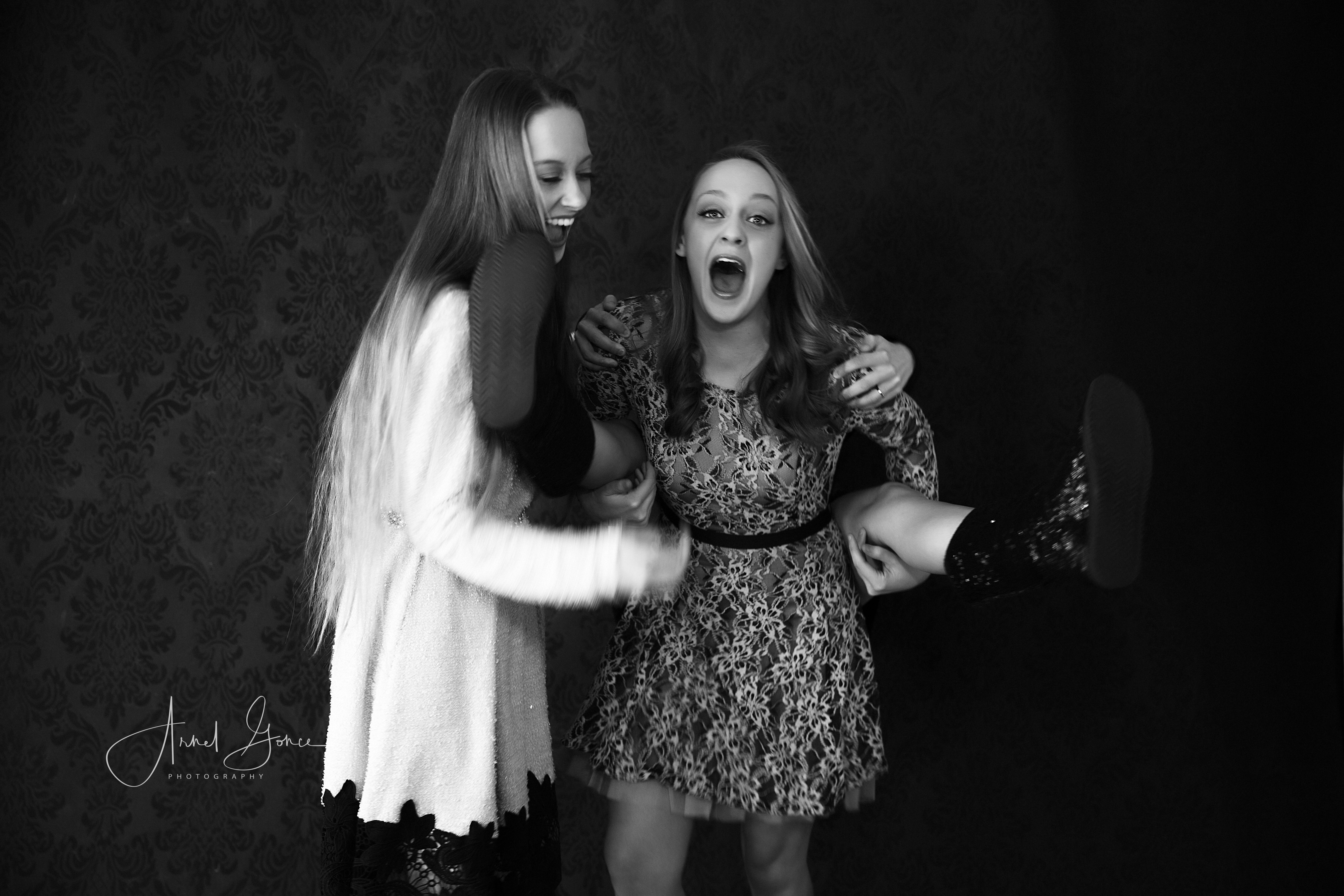 Black and white photograph of sisters horsing around during their photoshoot.